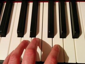left hand on piano keys